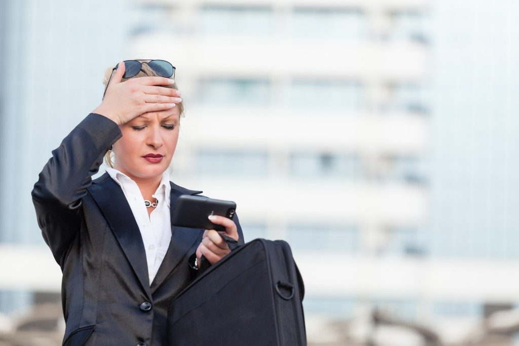 a worried businesswoman using her phone