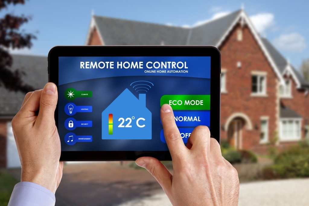 Holding a smart energy controller or remote home control online home automation system on a digital tablet.