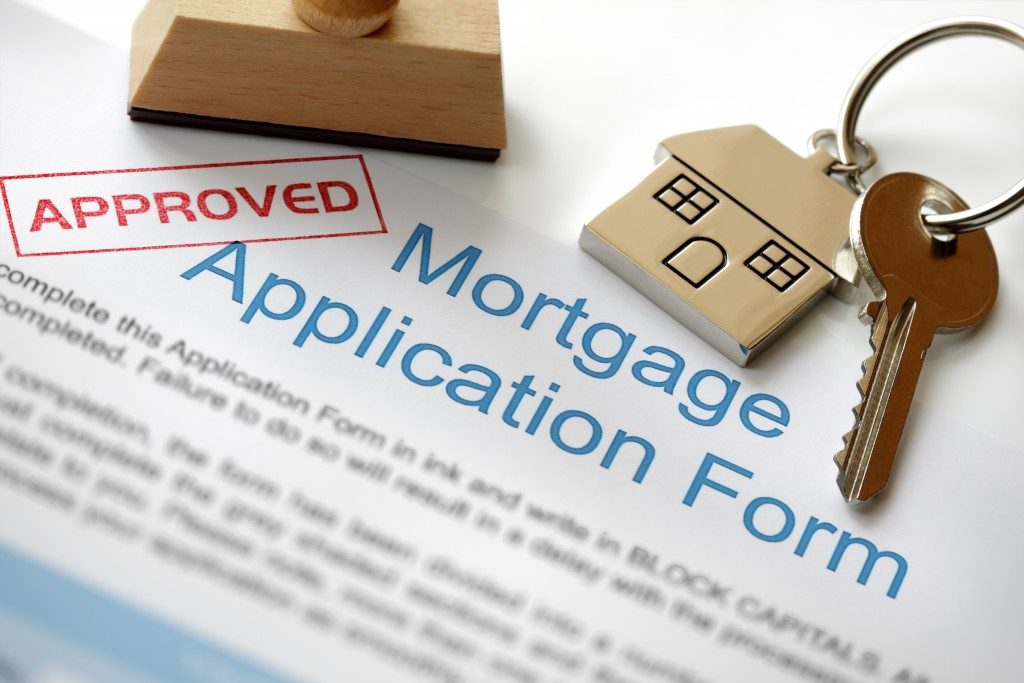 Approved Mortgage loan application with house key and rubber stamp