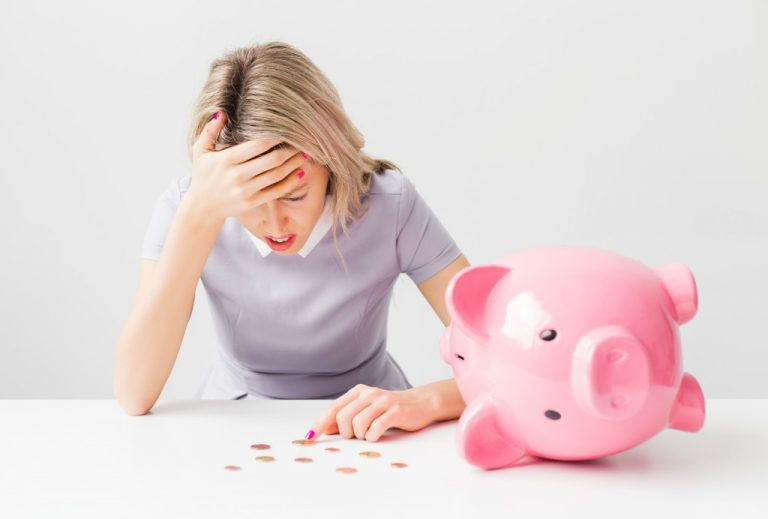woman stressed out while counting coins from a piggybank
